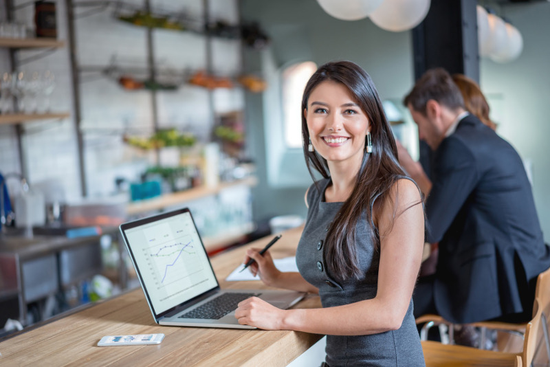 Happy business woman working at a cafe on a laptop and looking at the camera smiling. Image on screen is own design.